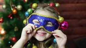 Uma menina com as festões do Natal em sua cabeça em uma máscara do carnaval vídeos de arquivo