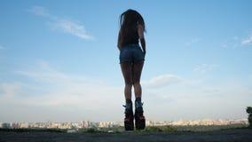 Uma menina com uma boa figura é contratada na aptidão em saltos do angoo das sapatas, ar fresco 4K mo lento video estoque