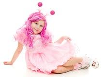 Uma menina com cabelo cor-de-rosa em um vestido cor-de-rosa Fotos de Stock Royalty Free
