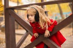 Uma menina com cabelo louro joga na cerca de madeira foto de stock