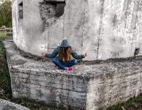 Uma menina com cabelo louro longo em uma capa senta-se em uma pose dos lótus Fotos de Stock Royalty Free
