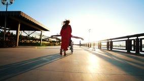 Uma menina com cabelo vermelho em um vestido alaranjado Rolls um enfermo Guy Who Raised His Hands aos lados vídeos de arquivo