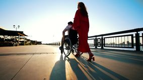 Uma menina com cabelo vermelho no vestido alaranjado Rolls um enfermo Guy In uma cadeira de rodas na margem no por do sol filme