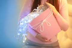 Uma menina com caixa de presente e luzes cor-de-rosa imagem de stock royalty free