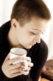 Uma menina com chá bebendo do corte de cabelo curto Foto de Stock