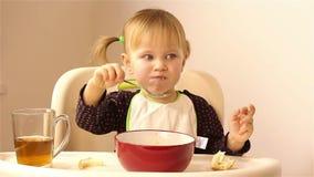 Uma menina com dois anos pequena come o papa de aveia vídeos de arquivo