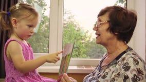 Uma menina com dois anos pequena joga com sua avó filme