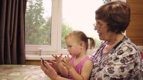 Uma menina com dois anos pequena joga com sua avó video estoque