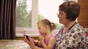 Uma menina com dois anos pequena joga com sua avó vídeos de arquivo