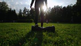 Uma menina com uma figura delgada bonita que monta um giroscópio na grama no parque no verão O sol está brilhando video estoque