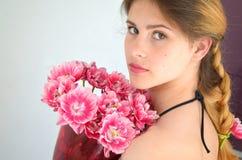 Uma menina com hairdress bonitos com um ramalhete das tulipas é meio um Columbo Imagens de Stock Royalty Free