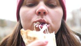 Uma menina com olhos com fome come o shawarma com prazer, vegetais cola fora de sua boca HD, 1920x1080, movimento lento video estoque