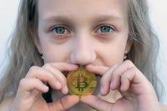 Uma menina com olhos verdes guarda uma moeda do bitcoin em sua boca Conceito do bitcoin f?cil que investe e que troca fotos de stock royalty free