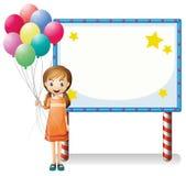 Uma menina com os balões que estão na frente de uma placa vazia Imagens de Stock Royalty Free