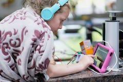 Uma menina com os fones de ouvido envolvidos em uma cobertura do velo fotografia de stock royalty free