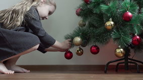 Uma menina com os pés desencapados que vêm à árvore de Natal e pendura uma festão em um ramo sob a forma das decorações do ` s do video estoque