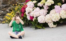 Uma menina com quatro anos coloca uma flor do cravo-de-defunto em seu cabelo fotografia de stock