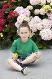 Uma menina com quatro anos na frente de diversas plantas de florescência foto de stock