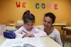 Uma menina com seu professor está preparando lições Fotos de Stock