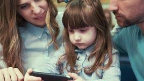 Uma menina com seus pais em um café, olhando o smartphone video estoque