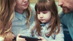 Uma menina com seus pais em um café, olhando o smartphone vídeos de arquivo
