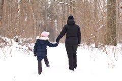 Uma menina com sua mãe na floresta do inverno o conceito da família foto de stock royalty free