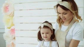 Uma menina com sua mãe usa um batedor de ovos para agitar a farinha A mãe ensina sua filha amassar uma massa vídeos de arquivo