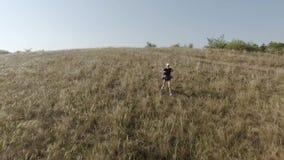 Uma menina com uma trouxa em seus ombros corre longe de uma inclinação íngreme Movimento lento filme