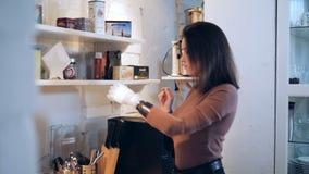 Uma menina com um braço protético toma um frasco com canela e abre-o video estoque