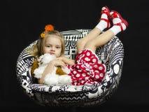 Uma menina com um brinquedo macio em uma cadeira Fotografia de Stock Royalty Free