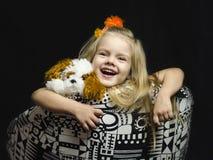 Uma menina com um brinquedo macio na cadeira. Foto de Stock