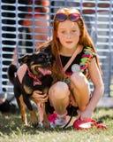 Uma menina com um cão no parque em uma exposição de cães imagens de stock