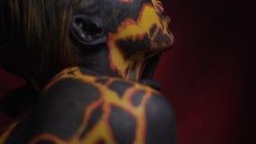 Uma menina com um corpo fantástico que pinta em geral o corpo move-se mystically durante uma dança em um fundo vermelho video estoque