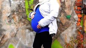 Uma menina com um embrião em seu estômago inclinou-se contra uma parede pintada com aerography vídeos de arquivo