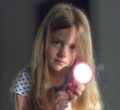Uma menina com um espelho e o sol, fazendo Sunny Bunny Fundo escuro imagens de stock