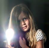 Uma menina com um espelho e o sol, fazendo Sunny Bunny Fundo escuro imagem de stock