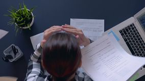 Uma menina com um humor mau que senta-se em uma tabela joga documentos acima e pega sua cabeça Movimento lento filme