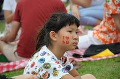 Uma menina com um lado de sua cara pintada durante um recolhimento em Marina Barrage Roof Garden fotografia de stock royalty free