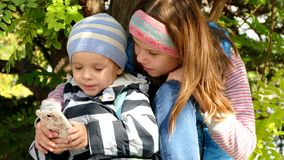 Uma menina com um menino está usando um smartphone vídeos de arquivo