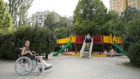 Uma menina com um pé quebrado senta-se em uma cadeira de rodas na frente do campo de jogos vídeos de arquivo
