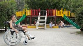 Uma menina com um pé quebrado senta-se em uma cadeira de rodas na frente do campo de jogos video estoque