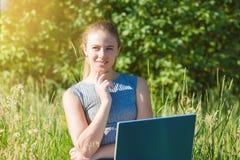 Uma menina com um portátil na natureza entre a grama verde fotos de stock