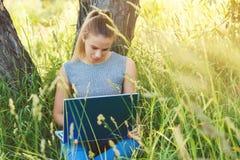 Uma menina com um portátil na natureza entre a grama verde imagens de stock royalty free