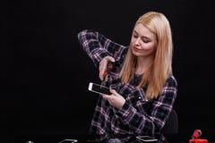 Uma menina, com um relance agradável, aperta um smartphone com uma tela quebrada Fundo preto imagem de stock royalty free