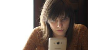 Uma menina com um smartphone em suas mãos filme