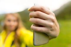 Uma menina com um telefone em sua mão fora Fotografia de Stock Royalty Free