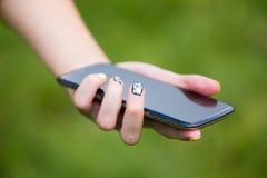 Uma menina com um telefone em sua mão fora Fotografia de Stock
