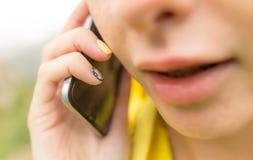Uma menina com um telefone em sua mão fora Imagem de Stock Royalty Free