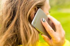 Uma menina com um telefone em sua mão fora Foto de Stock