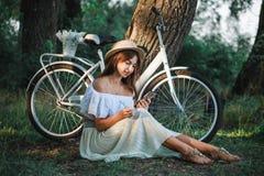 Uma menina com um telefone senta-se sob uma árvore Fotos de Stock Royalty Free